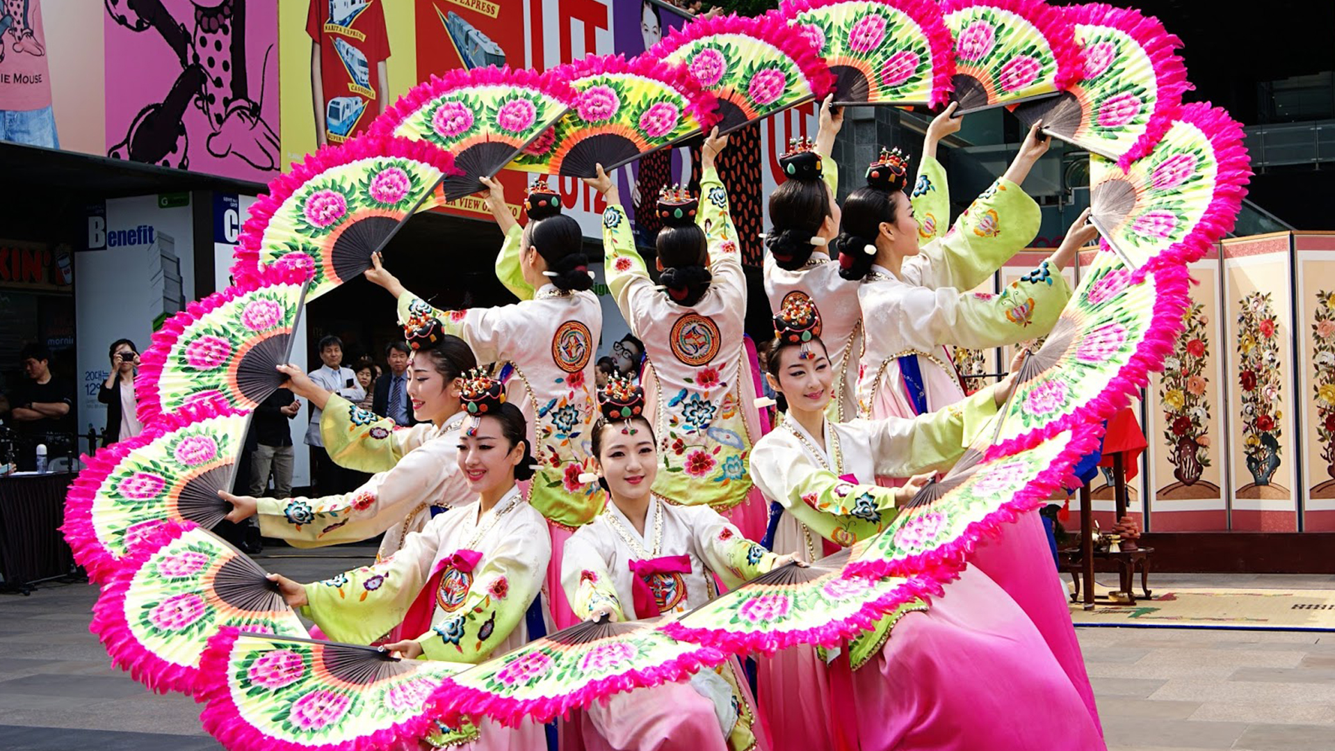 Buchaechum is a traditional form of Korean dance also called a fan dance, usually performed by groups of Korean female dancers. Koreans use this dance during many celebrations. Dancers use large fans painted with pink peony blossoms and display a show of dance. In the dance being performed, the dancers represent shaped images using the fans e.g. birds, flowers, butterflies and waves. They wear brightly coloured hanboks, the Korean traditional dress.