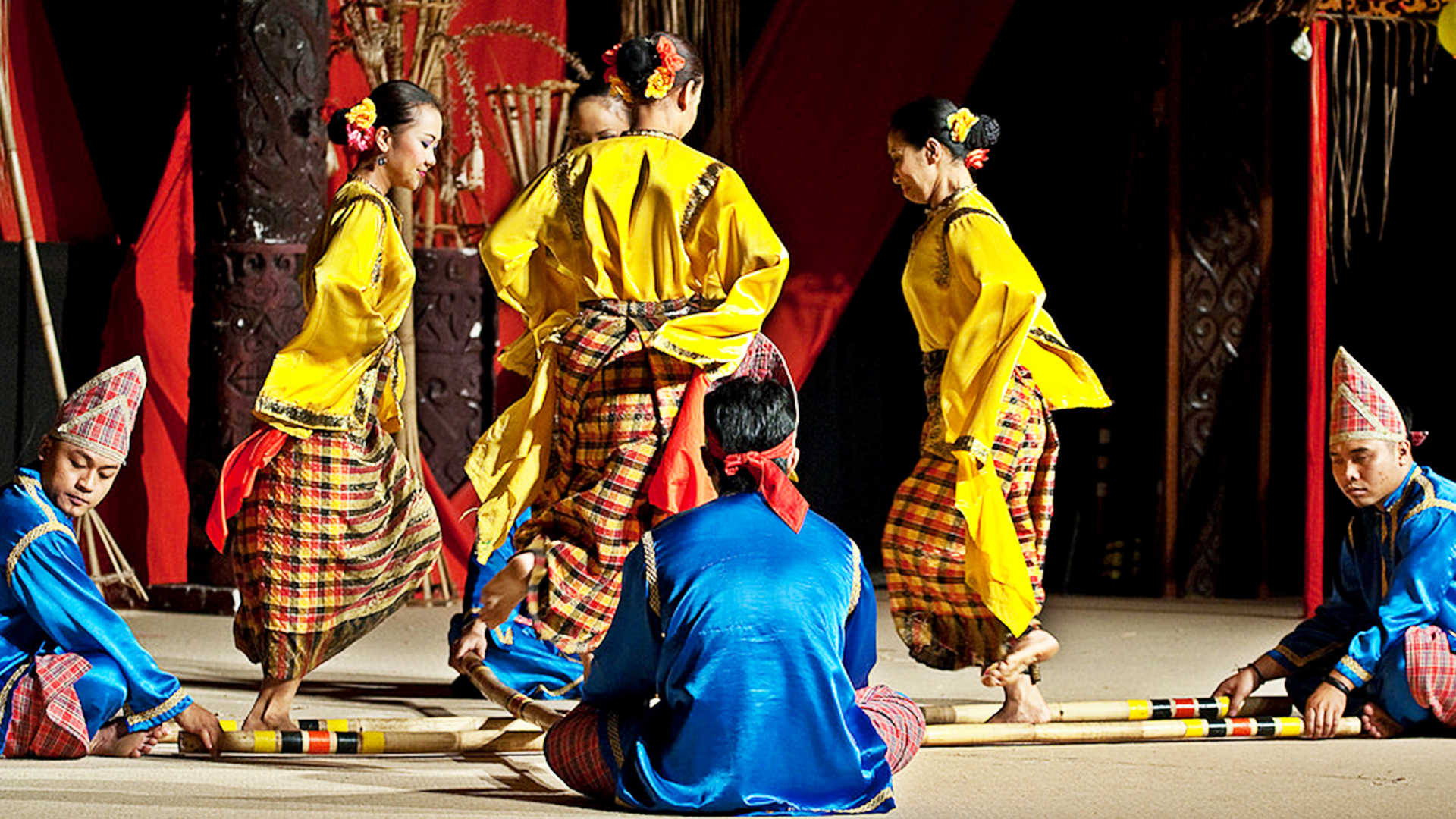 Tinikling is a traditional Philippine folk dance which originated during the Spanish colonial era. The dance involves two people beating, tapping, and sliding bamboo poles on the ground and against each other in coordination with one or more dancers who step over and in between the poles in a dance.